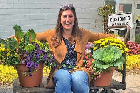 Erin Davidson, our Marketing Coordinator, wraps her arms around a pair of potted plants